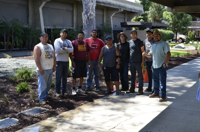 district gardeners and maintenance workers pose by plants