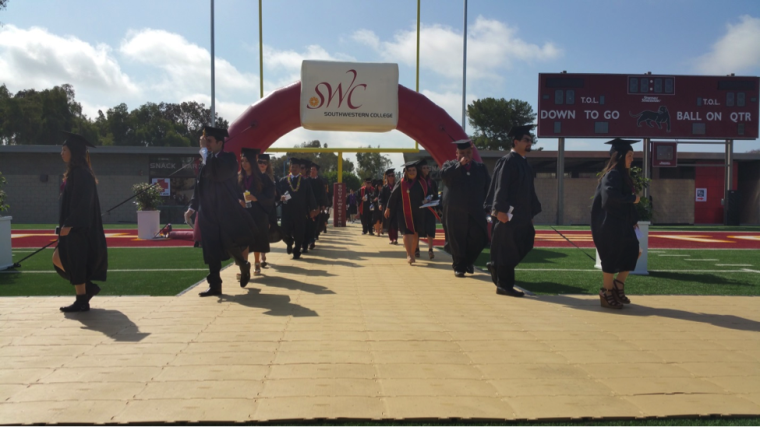 Graduates walk through the new arch as the Commencement ceremony begins.
