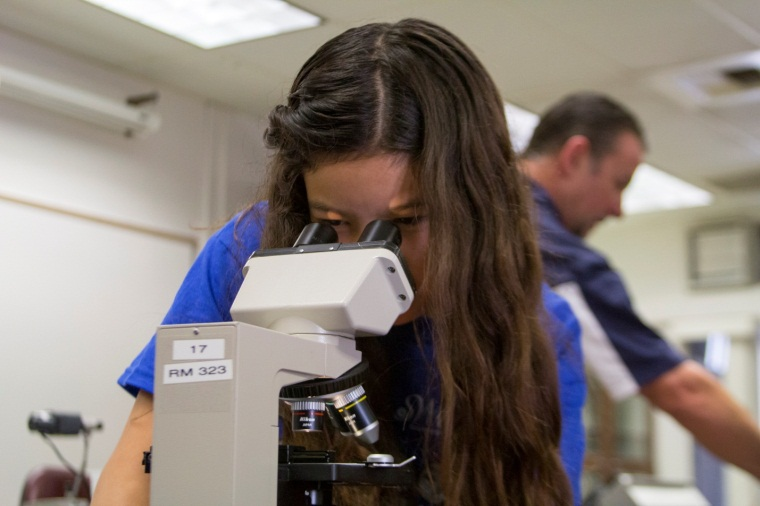 6th Grader Bibi Jimenez looks through microscope in College for Kids class