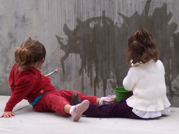 Photo of two children water painting