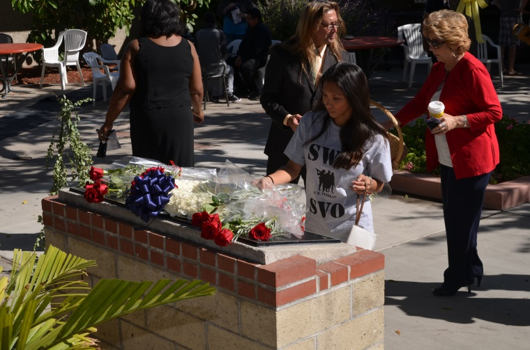 A student places a rose on the Veterans Memorial during the SWC Veterans Day Ceremony