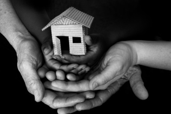 a black and white photo of a group of hands holding a small wooden house